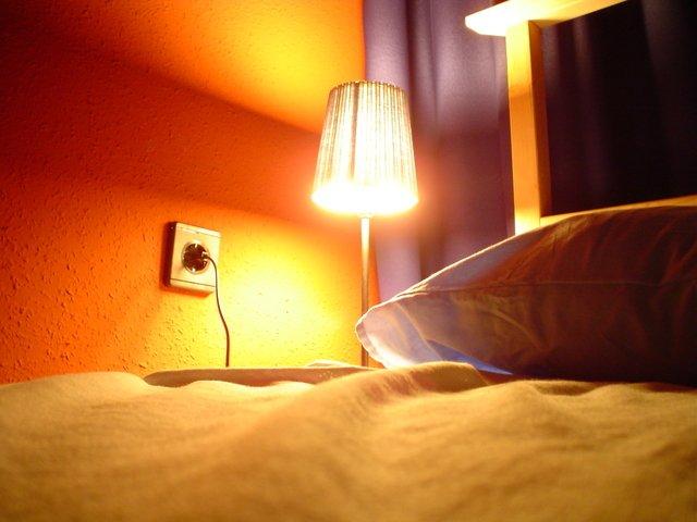 postel s rozsvícenou lampičkou